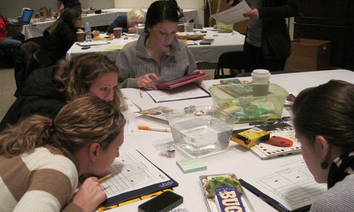 A group of teachers attentively watch an experiment during an educator workshop.