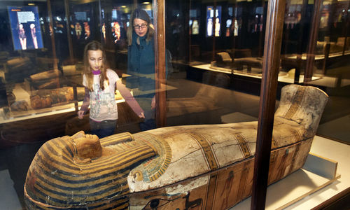 Women and girl looking at an Egyptian coffin in a glass case