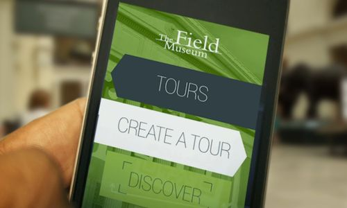 Hand holds mobile device that shows home screen of Field Museum Tours app.