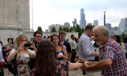 Young professionals gather around a woman with a tarantula on her arm at an event for Field Museum supporters. A staff member manages the crowd (and keeps an eye on the tarantula).