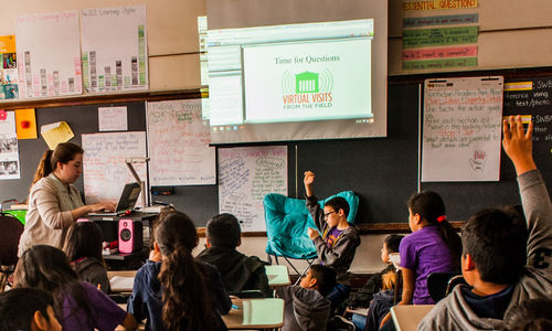 Students raise their hands as they sit in front of a screen in their classroom. Their teacher guides them through a Virtual Visit to The Field Museum.