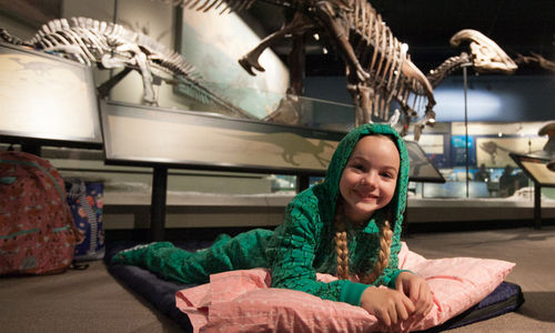 Girl wearing pajamas in dinosaur hall