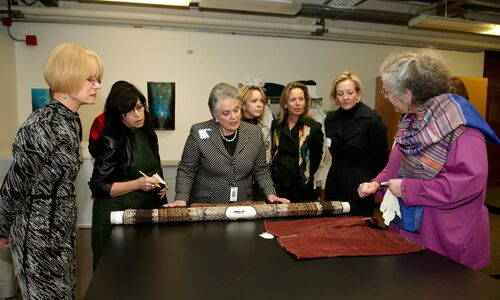 Members of the Women's Board view rolled and unrolled textiles from the collections on a behind-the-scenes tour.