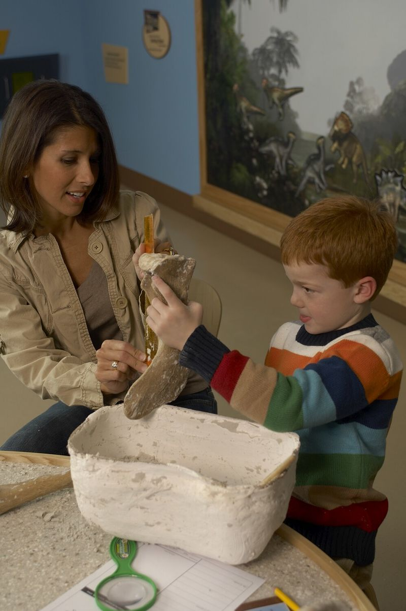 A woman helping a young boy measure a large bone with a ruler.