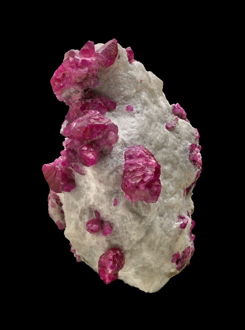 Several natural crystals of ruby in an irregular shaped white marble matrix.