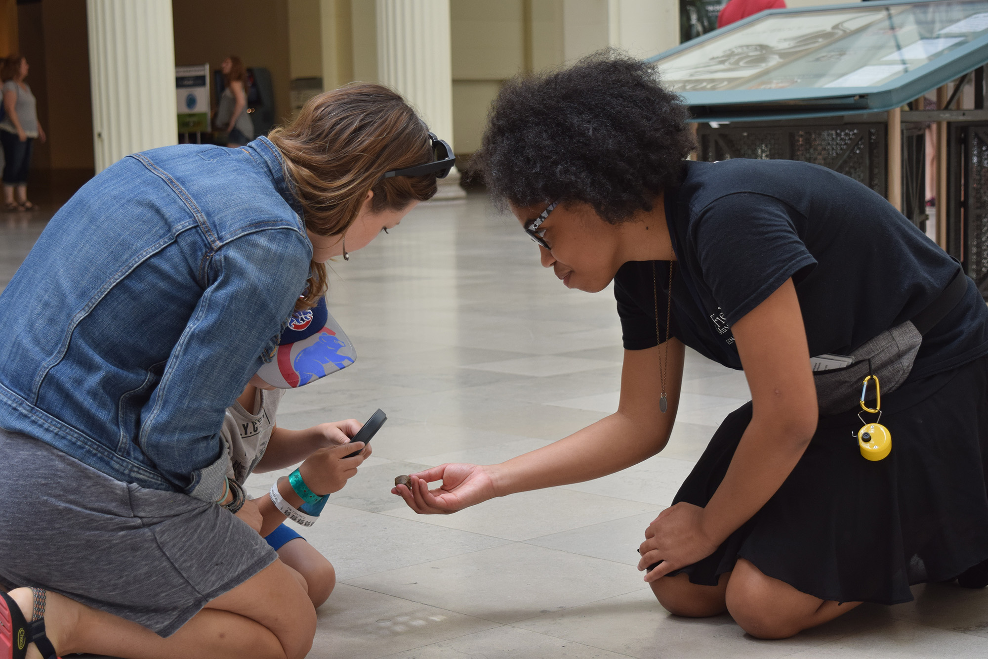 Two teens kneel on a tile floor next to a child. They are all looking at a small object one of the teens is holding out in her hand.