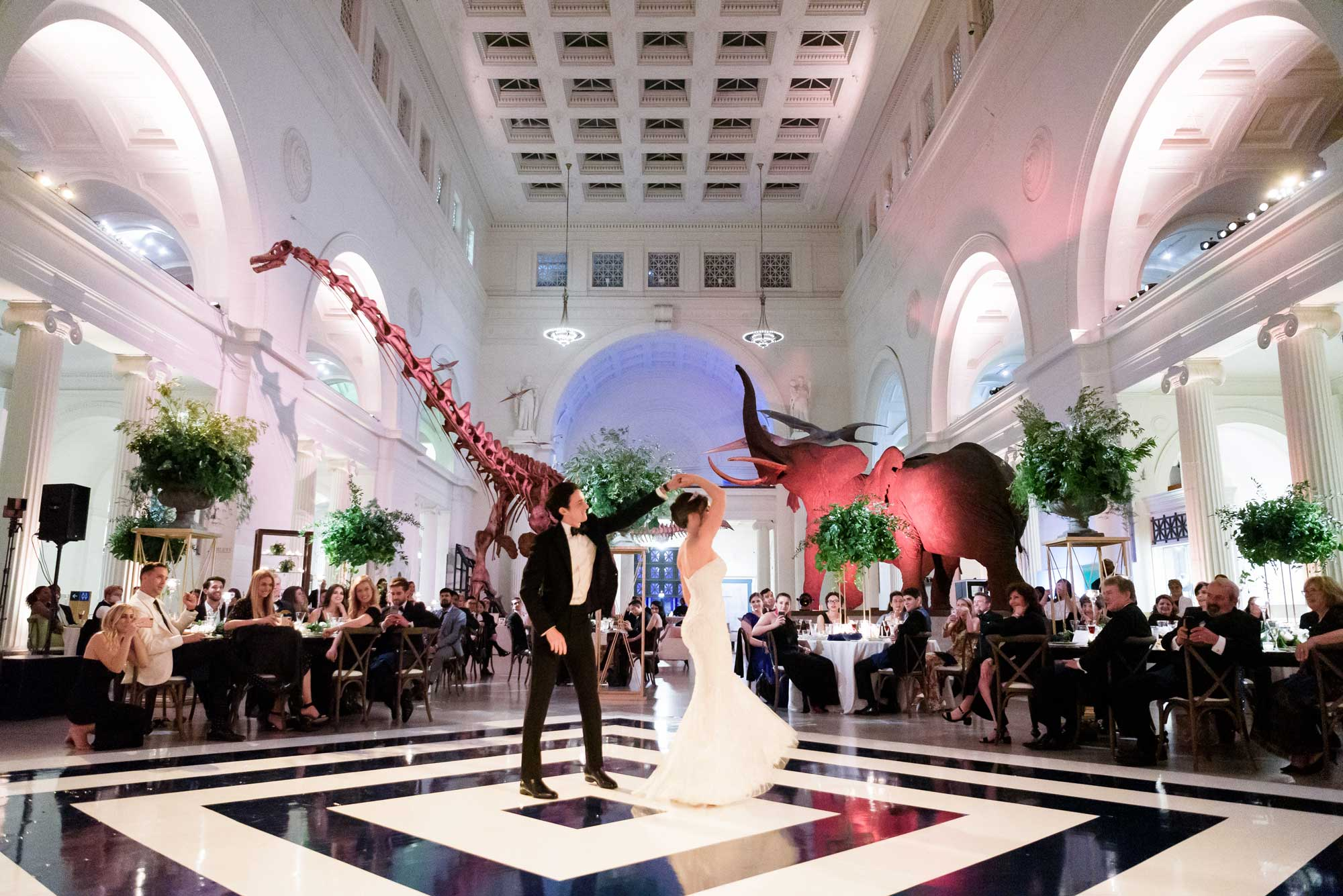 A couple shares their first dance in the center of Stanley Field Hall on a black and white dance floor. Wedding guests watch from their seats and elephants and Máximo the Titanosaur are visible in the background.